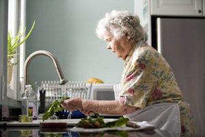 Een ouder vrouw doet de afwas
