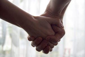 Twee handen die elkaar vasthouden